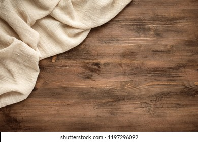 Sand color tablecloth from left top corner of old wooden table top view. Food background