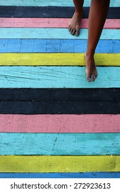 Sand covered feet on beach colorful deck