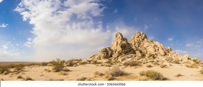 Sand desert holds pile of rock boulders forming a hill in the midst of the Mojave desert.