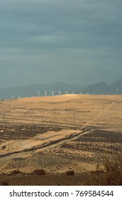 sand desert and wind power near the mountains under cloudy sky and road of car
