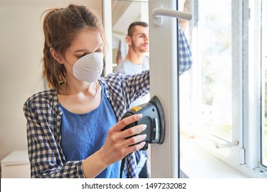 Sand down and restore young woman wearing a respirator mask by the window frame