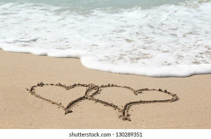 Sand drawing on warm beach by ocean surf in Caribbean with linked hearts
