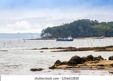 Sand dredge ship anchored in front of Cortegada Island national park on the Ulla river mouth in Carril village