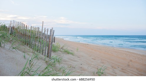 Sand dune fence in the foreground with beach in the background.  Shallow depth of field so foreground is in focus.