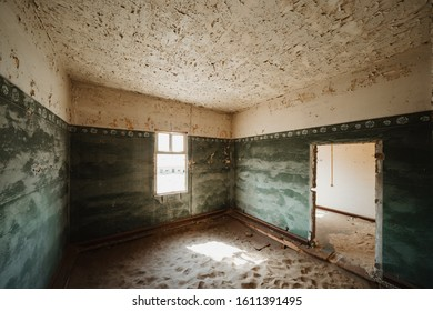 Sand Dune filling up abandoned Ghost Town House through doors and broken window