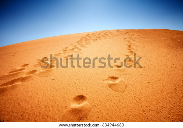 sand dune and foot prints, blue sky on background