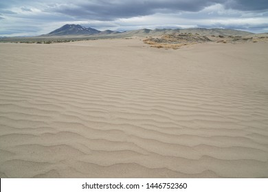 Sand dune in the foreground with a dramatic sky above