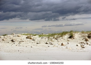 sand dune with grass and gray clouds in Camargue, France