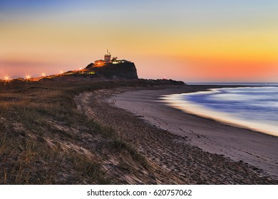 Sand dune with grass at Nobbys beach, nobbys head and lighthouse in Newcastle, NSW, at colourful orange sunrise.
