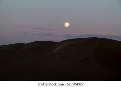Sand dunes in the desert near Huacachina, Peru. Moon is rising.