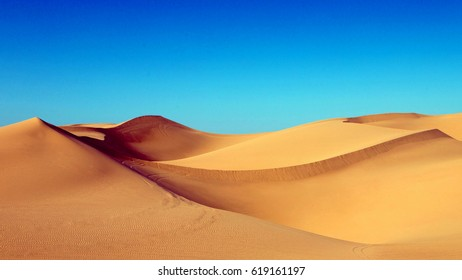 Sand dunes in the desert , warm dry sand under blue sky