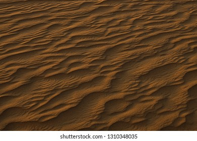 Sand dunes during sunset with long shadows, closeup in Dubai outskirts.