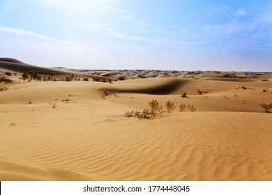 sand dunes in the Gobi Desert in Inner Mongolia, China. sandy desert with blue sky and apparent sun, few clouds, extraordinary travel scene. large expanse of sand as far as the eye can see