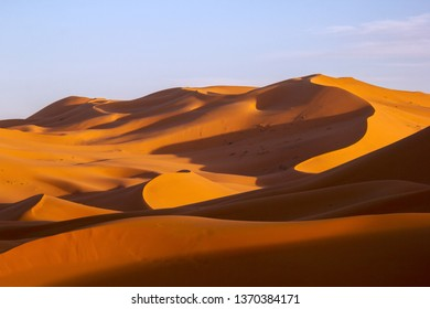 Sand dunes with lines and shadow in Sahara Desert under blue sunny sky