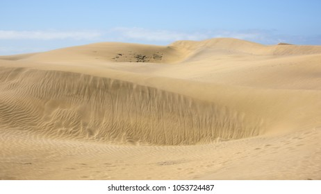 Sand dunes at Maspolamas, Gran Canaria, showing the natural patterns in the sand, created by the wind, and footprints.