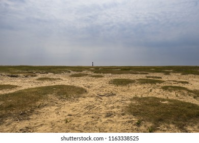 Sand dunes in Nordfriesland with a view of a lighthouse