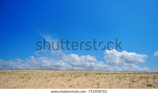 Sand dunes on blue sky background