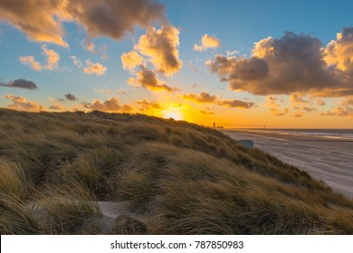 The sand dunes of Ostend and Bredene at sunset with the skyline and pier of Ostend in the background, West Flanders, Belgium.