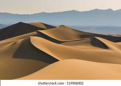Sand dunes over sunrise sky in Death Valley, California