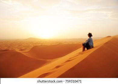 Sand dunes in the Sahara desert. Girl  between sand dunes. Lands