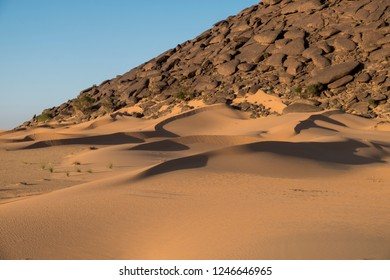 sand dunes in sahara desert with rock in the background