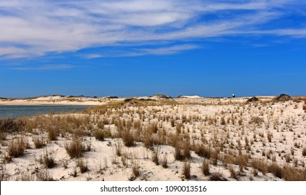 Sand dunes, sea grasses, coastline  and the harbor of refuge light on a sunny day at cape henlopen state park near rehoboth beach, delaware