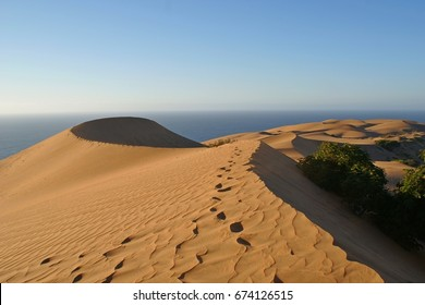 Sand dunes with shifting sands and the pacific ocean in background at vina del mare, chile