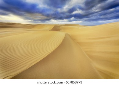 Sand dunes of Stockton beach in Australia under cloudy sky waving soft soil shaped by wind erosion.