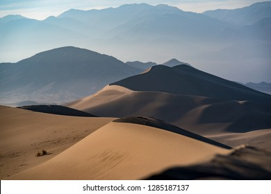 Sand dunes stretch for miles below towering Last Chance Mountains of California.
