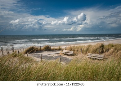 Sand dunes with tall grass and swaying sand in the wind on a sunny day with blue sky and white clouds. Beautiful photo of recreation along the Dutch sea coast.
