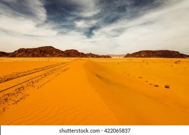 Sand dunes under dramatic  sky with sandy railroad, Wadi Rum, Jordan. concept of global warming.