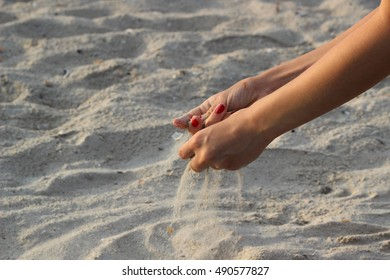 Sand from female hands crumbles in the wind
