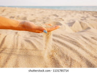 Sand flowing through female hand on shore near the sea.