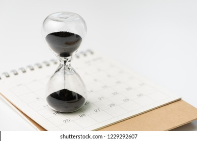 Sand glass or hour glass on white clean desktop calendar with white background and copy space using as time passing, year change or deadline concept.