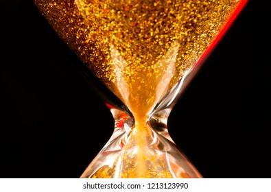 Sand and golden glitter passing through the glass bulbs of an hourglass measuring the passing time as it counts down to a deadline or closure on a black background with copy space