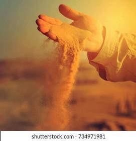 sand in hands of desert concept, vintage nature background