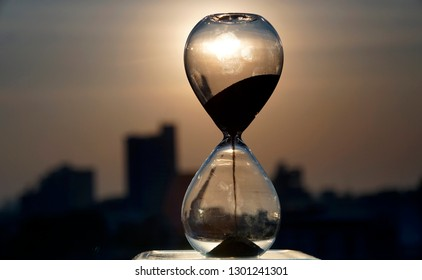 Sand in a hourglass is falling with blur city background in twilight time