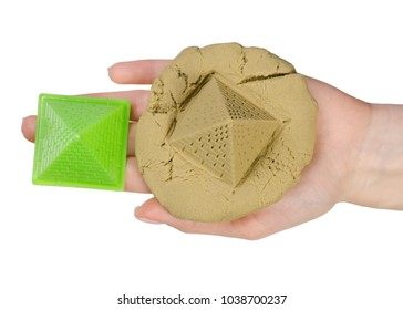 Sand kinetic pyramid on the hand on a white background isolation, top view