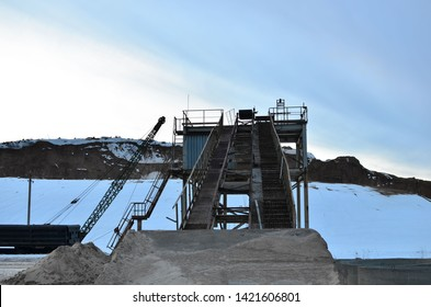 Sand mining in winter conditions in an industrial quarry. Conveyor Belt in mining quarry, Mining industry. Amazing mountains against the backdrop of snow and industry
