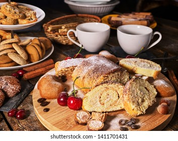 Sand nut chocolate cookies and rolled biscuit on board and cinnamon stick and straw pastry on kitchen on wood table in rustic style top view. Cups of tea and dessert spoon. Eat in small portions.