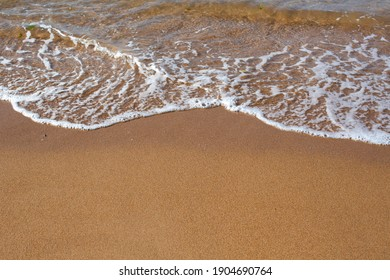 Sand on the beach with a sea wave