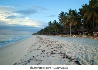 Sand paradise beach on the Indian Ocean and palm trees at sunset in a local resort in Kenya, East Africa.