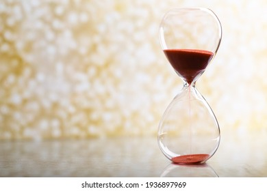 Sand passes through an hourglass, measuring the travel time in a countdown against a golden bokeh background