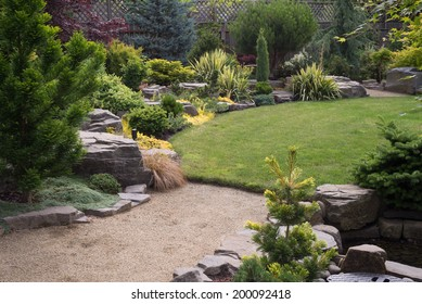 A sand pebbled path leads to a lush green backyard lawn featuring naturally sculptured rocks and a variety of small trees and shrubs