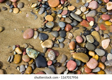 Sand and pebbles of various colors on a Mediterranean beach