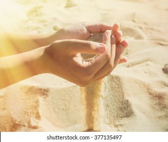 Sand pours through the fingers of a young girl on the beach on a hot summer day. Left falling sunlight. Selective focus image for materials about summer vacation or life philosophical topics