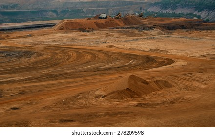 Sand quarry / Brown coal quarry / Bunk wall surface mine with exposed colored minerals and brown coal, mining equipment at the bottom the pit, view from above, top view