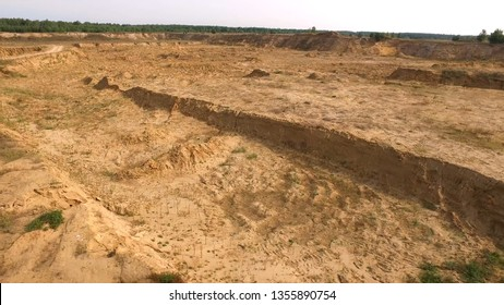 Sand quarry in countryside. Scene. Top view of empty yellow quarry with roads and pits on background of greenery and forest area in summer