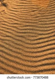 Sand ripples on an ocean beach at sunset