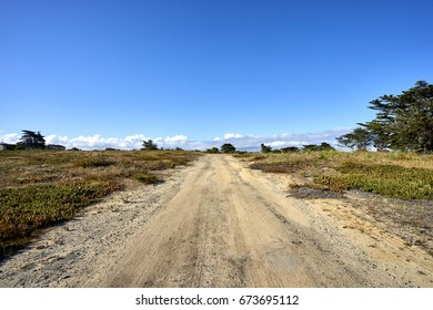 Sand road towards deserted buildings on military installation